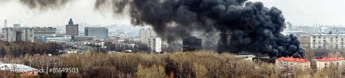Fotobehang Vuur / Vlam Column of black smoke rising above fireplace in the city