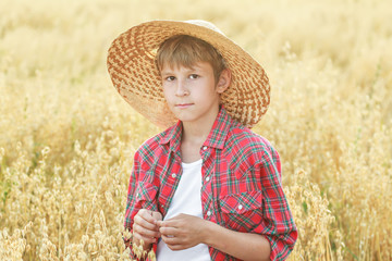 Teenage farm boy wearing checkered shirt and wide-brimmed hat
