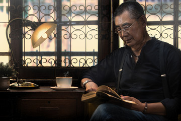 Man reading book and drinking coffee
