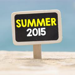 Summer 2015 text written on chalkboard, on sandy beach