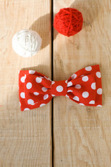 Tie fabric with red polka dots and two bright balls of yarn