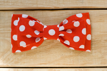 Tie fabric with red polka dots lie on a light wooden background