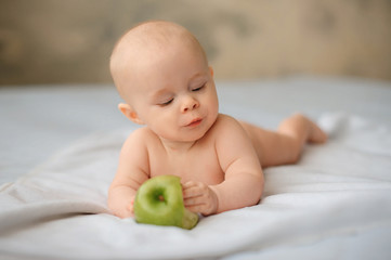 Cute baby with a huge green apple, health, lifestyle