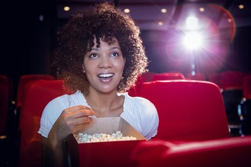 Smiling young woman watching a film