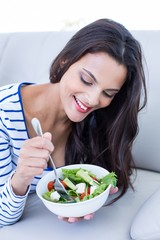 Smiling beautiful brunette eating salad on couch