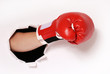 Hand in boxing glove through paper hole - 81652312