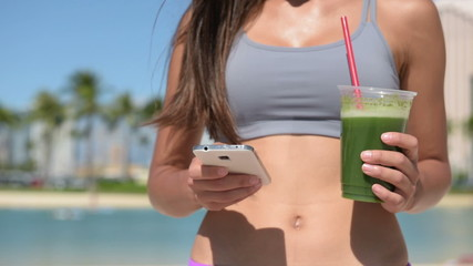 Sexy Woman with Green Juice Busy with Phone App