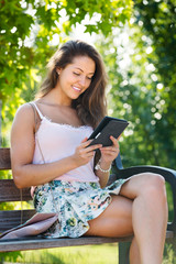 Girl sitting on bench with ereader