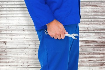Composite image of mechanic holding spanners on white background