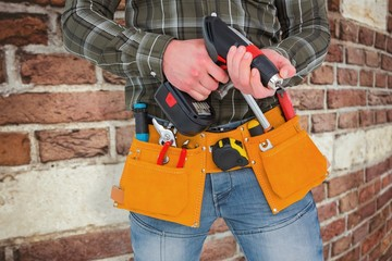 manual worker holding gloves and hammer power drill