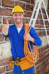 Male technician with wire roll gesturing thumbs up