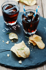 Potato chips and glass of cola on the table