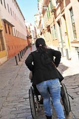 Anciana en silla de ruedas y ayudante