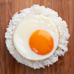 fried egg with steam rice on wooden table