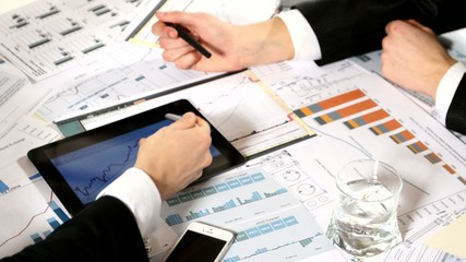 Business negotiations: a tablet with graphs on the table