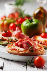 Mini pizza with mozzarella, prosciutto and tomato
