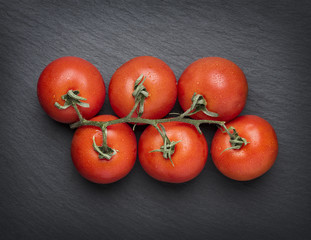 Tomatoes isolated on stone plate.