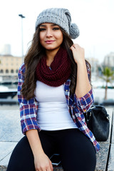Gorgeous young hipster girl sitting on a bench looking to you