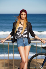 Hipster girl standing with sport fixed gear bike on the beach