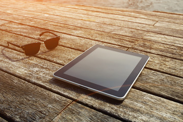 Sunglasses and digital tablet lying on wooden jetty at sunny day