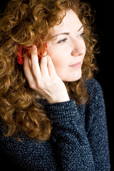 Portrait of beautiful young redhead with curly red rose