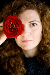 Portrait of beautiful young redhead with curly red rose in hand