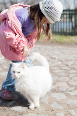 Cute little girl stroking white cat