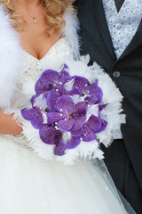 wedding bouquet of purple orchids and feathers