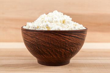 Fresh cottage cheese in a bowl on a wooden.