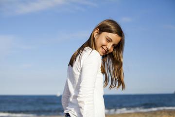 Niña de pelo castaño con camisa blanca en la playa