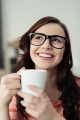 lachende frau mit kaffeetasse in der hand