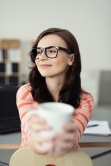 entspannte frau mit einer tasse kaffee am schreibtisch
