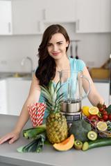 lächelnde junge frau mit obst und mixer in ihrer küche