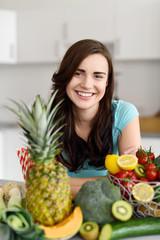 lächelnde frau mit obst und gemüse in ihrer küche