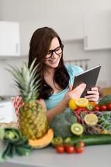 frau mit tablet-pc und viel obst und gemüse