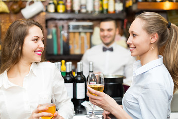 Bartender and two girls at bar