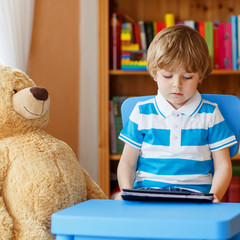 preschool kid boy playing with tablet computer in his room at ho