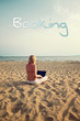 blond woman sitting on sunny beach with laptop - holiday booking