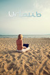 blond woman sitting on sunny beach with laptop