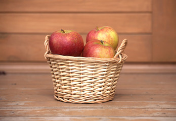 Ripe red and yellow apples in light brown wicker basket closeup
