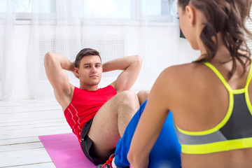 Active sportive man doing abdominal exercises crunches on floor