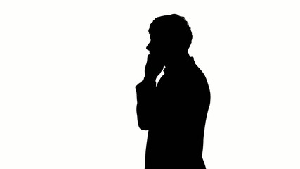 Black silhouette of man typing on mobile telephone