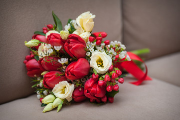 Beautiful wedding bouquet of red tulips lying on the sofa