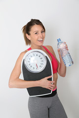 Cheerful fitness girl with bottle of water, isolated