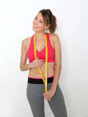 Fitness girl on diet with measure tape around neck, isolated