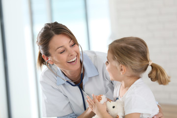 Doctor examining little girl with stethoscope