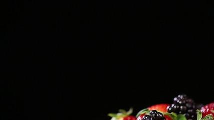 Fresh tasty berries on black background