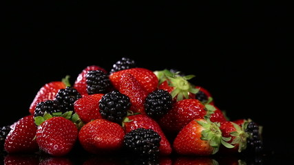 Fresh tasty berries on black background