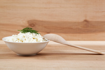 Fresh cottage cheese in a white bowl with spoon on a wooden boar