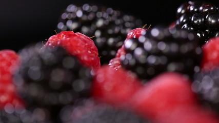 Fresh blackberries and raspberries on black background